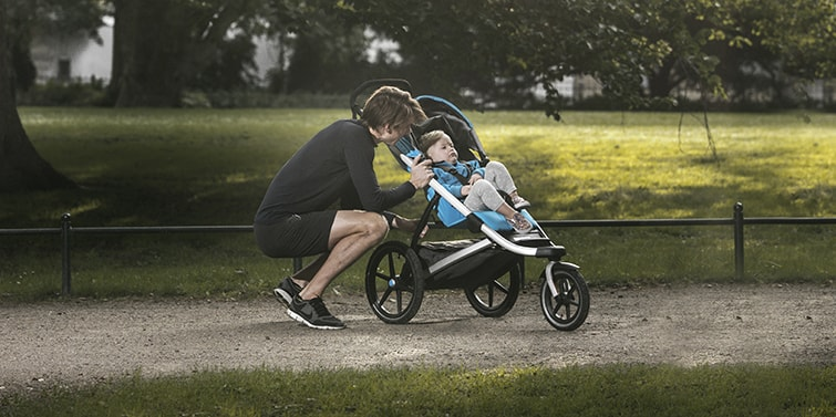 Two babies in a running buggy from Thule